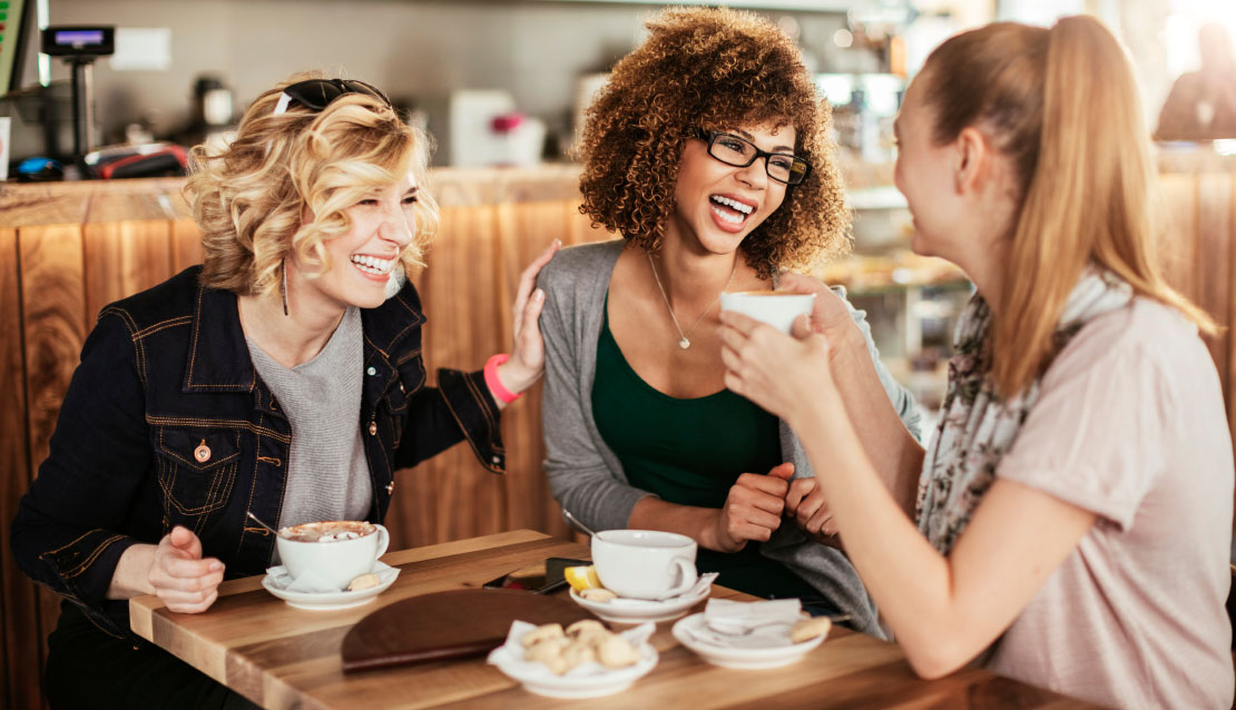 Women laughing at a coffee shop